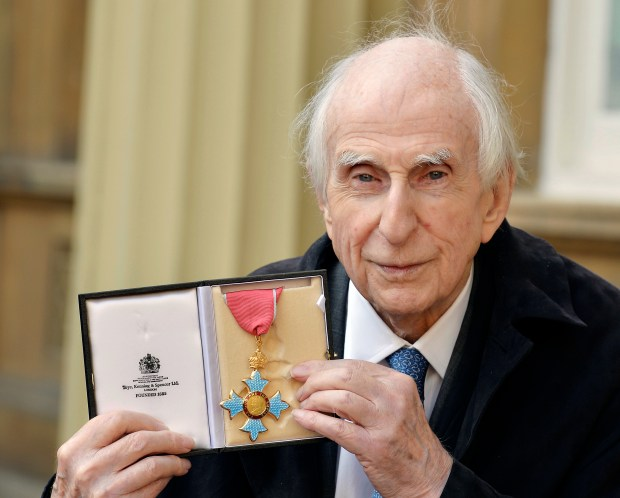 FILE - In this Oct. 27, 2015 file photo, Michael Bond, the creator of Paddington Bear, poses with his Commander of the Order of the British Empire (CBE). Publisher HarperCollins says Michael Bond, creator of globe-trotting teddy Paddington bear, died on Tuesday June 27, 2017, aged 91. (John Stillwell/PA via AP)