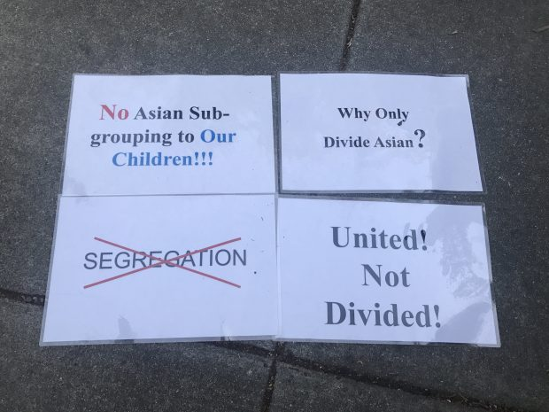 An example of signs parents held at a Pleasanton Unified School District meeting against subdividing of Asian groups.