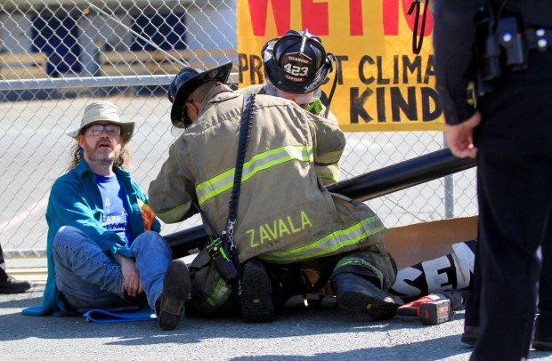 Stardust Doherty from San Francisco sings a protest song as firefighters cut through the pipe covering his and another protester's hands as they extricate them from blocking a gate at the Kinder Morgan terminal in Richmond, Calif., on Monday, July 24, 2017. (Laura A. Oda/Bay Area News Group)