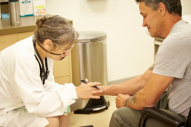 Dr. Vona Lorenza, medical director at The Order of Malta Clinic of Northern California in Oakland, examines patient Fred Pons of San Francisco.