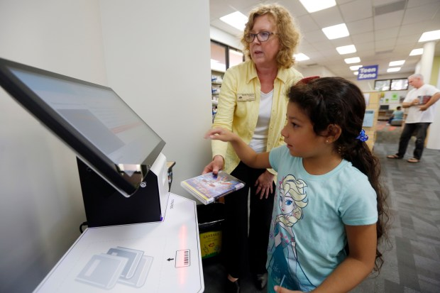 Branch Manager Sarah Hodgson helps 7-year-old Merlin Meza at the self-check out station at the newly refurbished Oakland Public Library, Dimond branch on Tuesday. (Laura A. Oda/Bay Area News Group)
