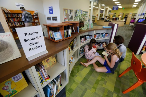 Kathie Rhodes, right, with Eliza King, 9, center, and Yuzuka Williams, 10, look for audio books for an upcoming road trip in the children's area at the newly refurbished Oakland Public Library, Dimond branch on Tuesday. (Laura A. Oda/Bay Area News Group)