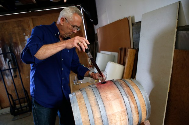 Wine maker Tom Kramer moves wine from a barrel into a glass at his Oakland hills home. (Aric Crabb/Staff)