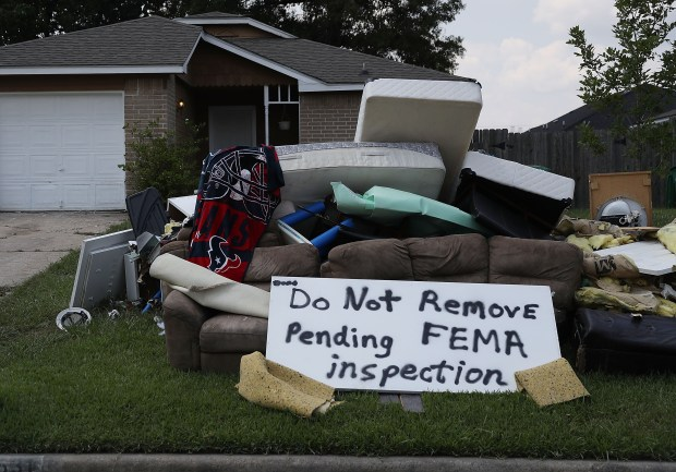 """HOUSTON, TX - SEPTEMBER 02: A sign reads, """" Do Not Remove Pending FEMA inspection', is seen with water logged items that were placed on the curb in front of a home as people start to rebuild their homes that were inundated with water after torrential rains caused widespread flooding during Hurricane and Tropical Storm Harvey on September 2, 2017 in Houston, Texas. Harvey, which made landfall north of Corpus Christi on August 25, dumped around 50 inches of rain in and around areas of Houston and Southeast Texas.  (Photo by Joe Raedle/Getty Images)"""