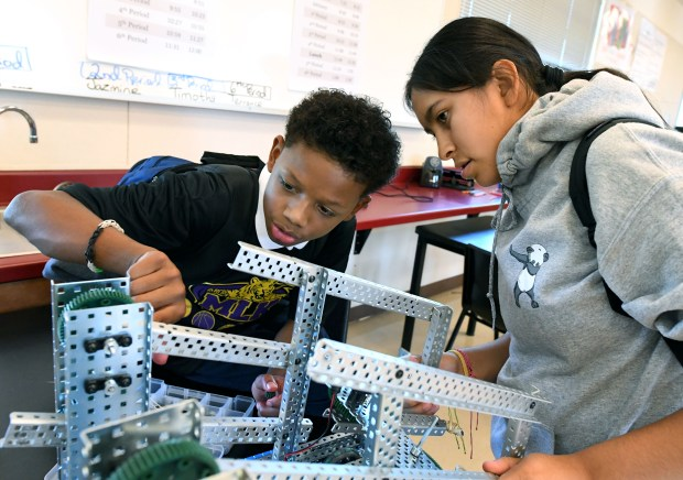 Martin Luther King, Jr. Junior High School students and robotics club members Nias Gomez, 12, and Thalia Guzman, 14, work on a robot in Pittsburg, Calif., on Thursday, Oct. 26, 2017. The robotics club is run by science and robotics teacher Shaw'sae Dodson. Last year Chevron granted money to the school to fund the robotics curriculum and materials through a program called Project Lead the Way. (Doug Duran/Bay Area News Group)