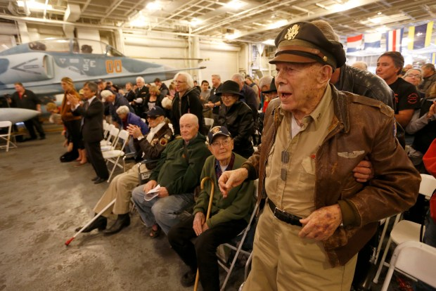 Former World War II Army Air Corp Lt. David Campbell, right, is helped to his feet by his son Glen Campbell, both of San Mateo, as they listen to Pearl Harbor survivor Chuck Kohler, 93, tell his first-person account during a remembrance marking the 76th anniversary of Pearl Harbor at the USS Hornet Museum in Alameda, Calif., on Thursday, Dec. 7, 2017. To the right is KCBS radio's Stan Bunger. Pearl Harbor was bombed on Dec. 7, 1941, killing 2,403 Americans and wounding 1,178 on the island of Oahu. (Jane Tyska/Bay Area News Group)