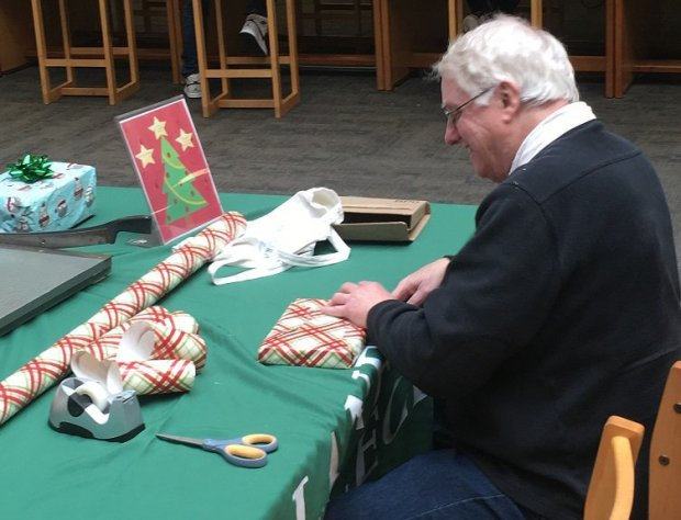 Scott Strain, a journalism instructor at Laney College, takes advantage of a gift-wrapping station set up at the college's library.