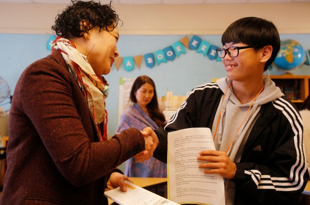 Woo Williams-You, middle school director, talks with South Korean student Myeongho Son, 15, during a lunch break at the Academy of Alameda in Alameda, Calif., on Monday, Jan. 22, 2018. (Laura A. Oda/Bay Area News Group)