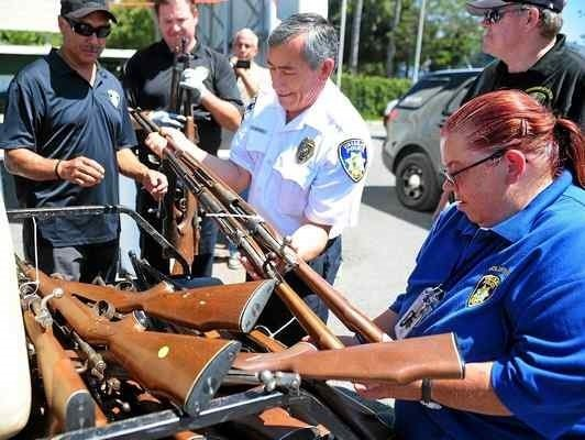 Carlos Martinez and Anne Fennessy with the Vallejo Police Department'sCitizens on Patrol help unload a pile of guns during the Buy Back Our Future gun buyback event at the Solano County Fairgrounds on Aug. 26, 2017, in Vallejo. A man in a van had just surrendered the pile of 32 firearms. (Chris Riley—Times-Herald)