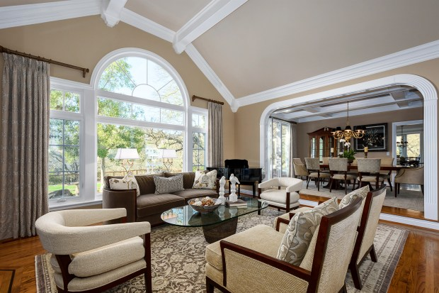 The elegant formal living and dining rooms are defined by columns and arched entries.
