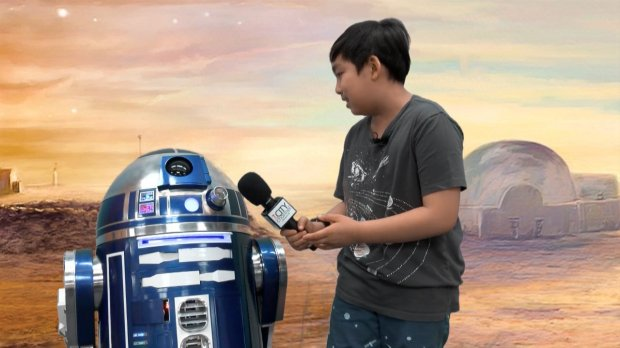 """Volunteer Samuel Chen interviews an R2 droid at """"Night of 1000 Inventions2015"""" for City Channel. Courtesy Larry Hunt"""