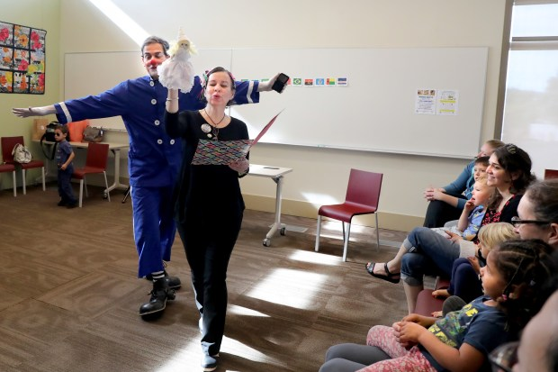 Portuguese language teacher and storyteller Tatiana Dutraemello, followed by clown Frangolino perform during a children's story time in the Portuguese language at the Lafayette Library and Learning Center in Lafayette, Calif., on Saturday, Feb. 10, 2018. The Lafayette Library and Learning Center has several foreign language children's story time programs for the pre-school set. They read books in English, Spanish, Mandarin, French, Portuguese and Farsi. (Ray Chavez/Bay Area News Group)