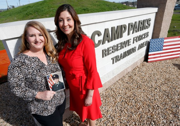 Dublin Citycouncilwoman Melissa Hernandez-Strah, right, and Army veteran and Dublin Parks Commission member Janine Thalblum, holding a picture of herself when she was in the Army, are photographed near the gate of the Camp Parks Reserve Forces Training Area in Dublin, Calif., on Thursday, Feb. 1, 2018. Dublin is joining a small yet growing group of cities that have set up a military poster program on utility poles as a way of honoring veterans. The idea was introduced in Dublin by Strah and Thalblum has been involved in launching it. (Jane Tyska/Bay Area News Group)