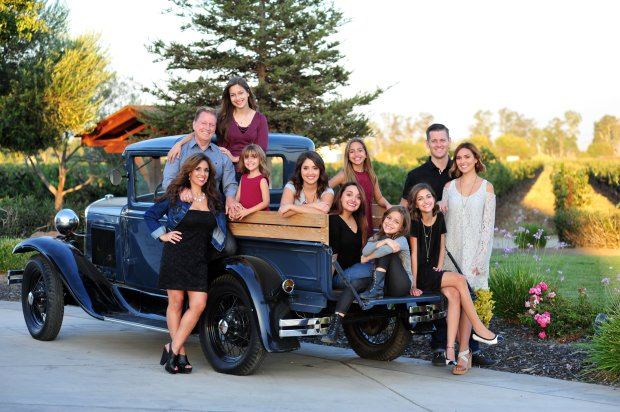 Ginamarie and Jeff Cornelius, of Brentwood, at left, pose with their familyof eight daughters and one son-in-law in happier times. Following her husband's heart attack, Ginamarie was left to raise her daughters on her own. Courtesy Ron Gilbert