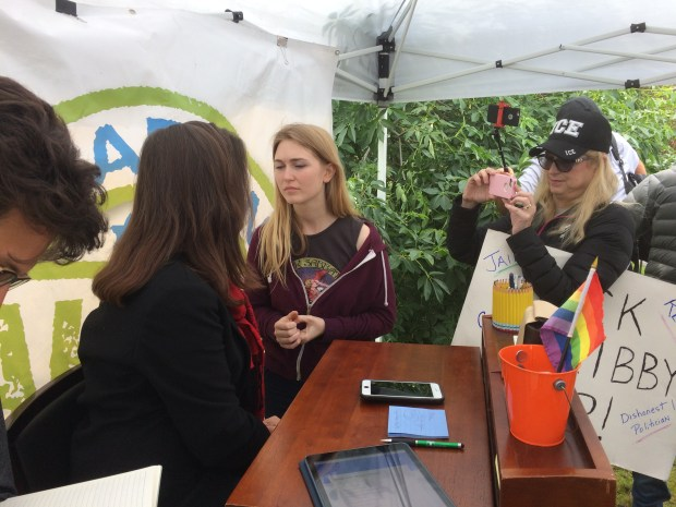 "Pro-President Trump protester Ashton Whitty speaks to Oakland Mayor Libby Schaaf Sunday, March 18, 2018 while another protester holding a ""Lock Libby Up!"" sign films Schaaf at the Temescal farmers market in the 5300 block of Claremont Avenue."