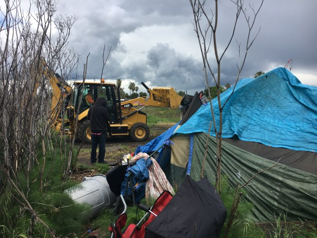 Homeless people looked on as a backhoe and dump truck removed all remaining tents and items from an encampment on McElheny Road in Antioch on Monday, April 16, 2018. (Aaron Davis/Staff)