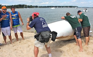 The capsized crew of Joseph Labrozzi, Jr.'s whaleboat mug for photos while their competitors, John K. Ott cesspool service, accustomed to cleaning up other people's messes, bail out their boat.