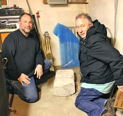 Custer Institute Vice President David van Popering and 375th Committeee member George Cork Maul with the mile marker in the basement of Custer Institute.