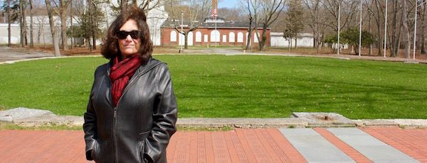 Tesla Science Center at Wardenclyffe President Jane Alcorn at the base of the former tower, with the lab in the background.