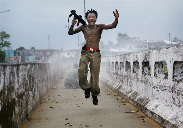 """Joseph Duo was a Liberian militia commander, immortalized by Hondros after firing a rocket-propelled grenade at rebel forces at a key strategic bridge on July 20, 2003, in Monrovia, Liberia."""