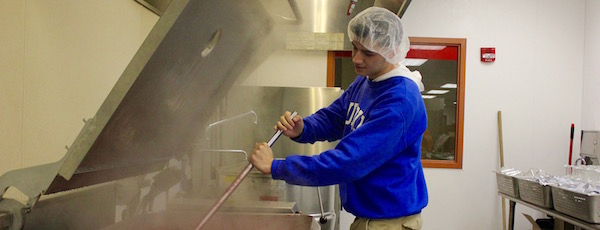 Sean Monegro stirs a vat of Kerbers Farms' cherry jam in the kitchens at the Stony Brook Incubator at Calverton.