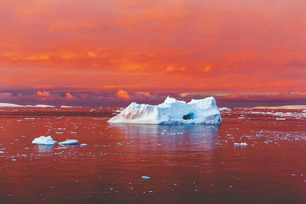 """Camille Seaman's """"Iceberg In Blood Red Sunset, Lemaire Channel, Antarctica, 2017"""""""