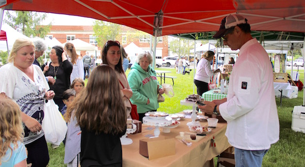 Crowds gathered in the spring showers Thursday afternoon for the opening day of the Hampton Bays Farmers Market.