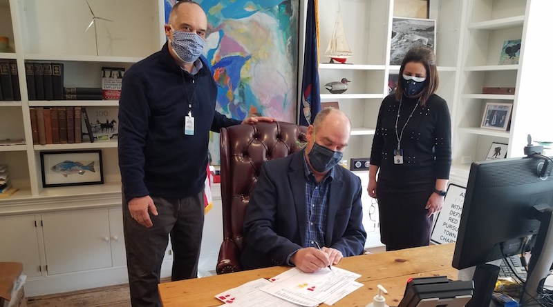 East Hampton Town Supervisor Peter Van Scoyoc signs off on the final payment on a 2011 bond issued to cover a $21.2 million budget deficit dating from a decade ago, while Len Bernard left, the town budget officer, and Neide Valeira, a senior accountant, look on.
