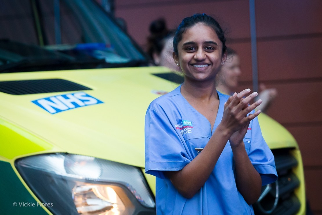 A nurse joins 'clap for carers' outside the Royal London Hospital