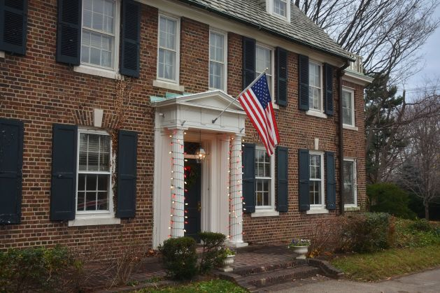 eastfallslocal-12-6-grace-kelly-house-front-steps-with-flag-christmas-lights
