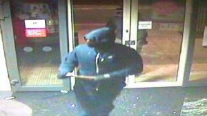CCTV image of gang breaking through plate glass door and entering Santander Bank New Malden. Pic: Met Police