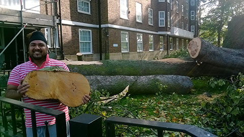 Gurpal Singh holding a piece of the tree that fell on his home. Pic: Chris Dillon