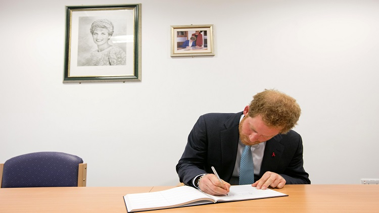 Prince Harry signs Mildmay's visitor's book in the Diana, Princess of wales Room Pic: Kois Miah