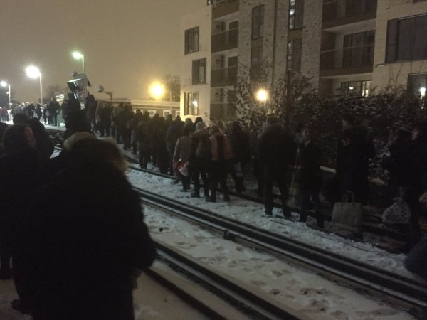People walking on snow-covered train tracks after leaving the stranded train. Pic: Nina Bevan @ninaEbevan