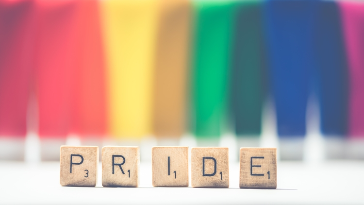 Rainbow paint with letters blocks that spell pride