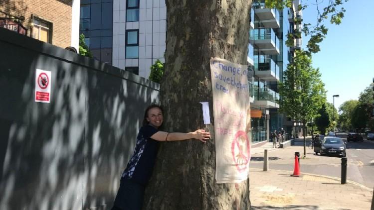 Protester hugging The Happy Man Tree. Picture: Arina Zinovyeva