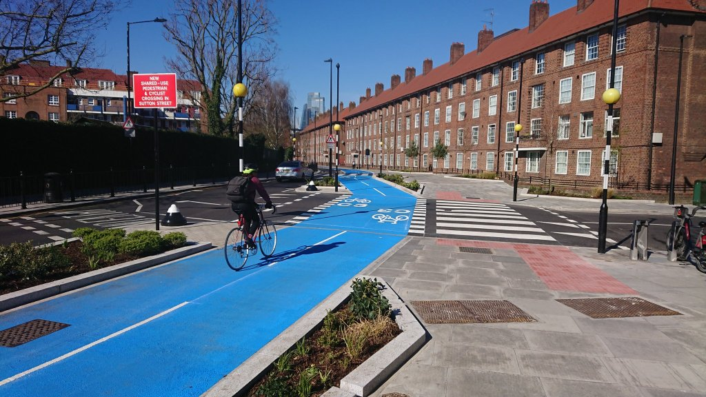 Photograph of a cyclist using the freshly painted crossing of Sutton Street in Tower Hamlets.