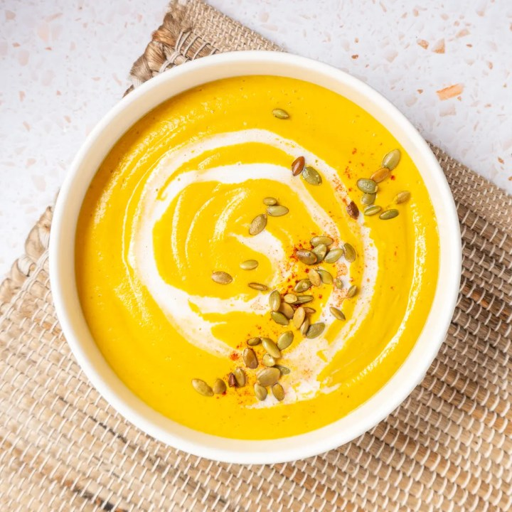 Bowl of Pumpkin Soup with pepitas and coconut milk on top