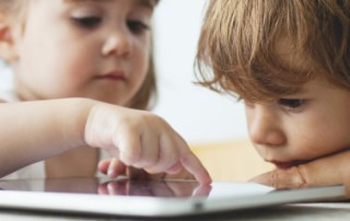 Small kids using a tablet before they learn to tie their shoes