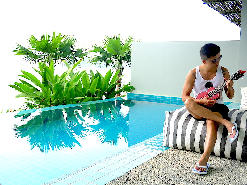 Evan playing ukelele by the pool