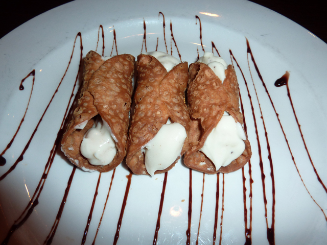 three canollis drizzled in chocolate sauce
