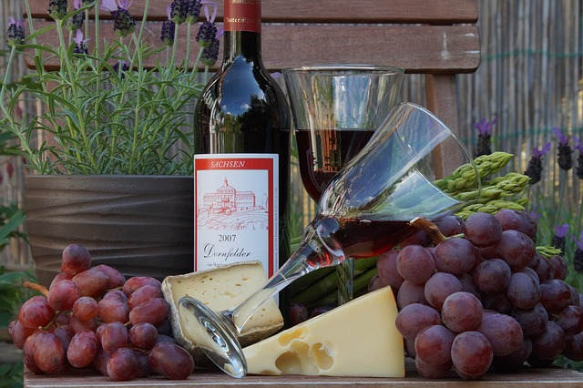 Image of bottle of red wine, cheese, grapes and wine glass.