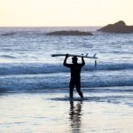 A surfer wading out to sea who's read up on a healthy food blog