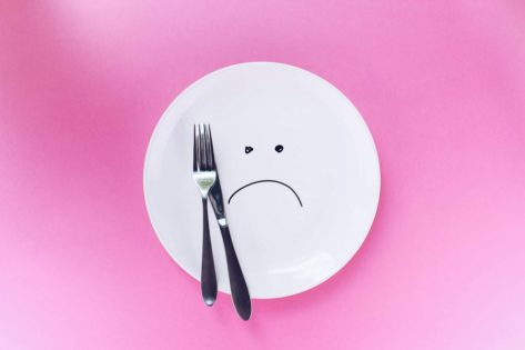 silver fork and knife on empty plate with sad face drawn on plate