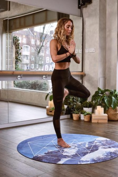 Woman doing yoga near glass window