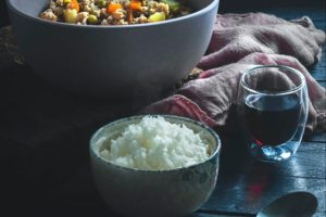 White Ceramic Bowl with White Rice; Gray Bowl with Beans and Vegetables on a Dark Table.