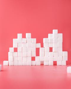 Stack of sugar cubes on pink background