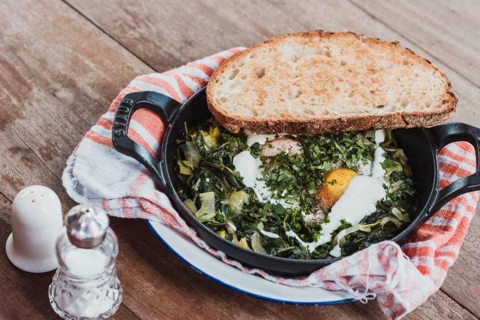 A sklillet with eggs and a Spinach bake, as featured on a blog about healthy eating hacks