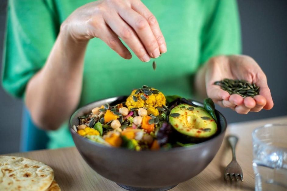 A woman sprinkling spices onto salad, as featured on a blog about healthy eating hacks