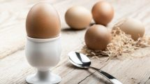 Spoon Next To White Egg Holder With Brown Eggs